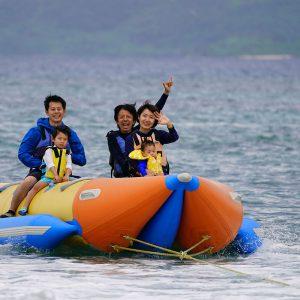 フサキビーチでドラゴンボ-トを楽しむ親子