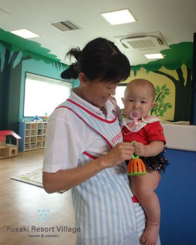 フサキの託児所で保育士にだっこされる女の子