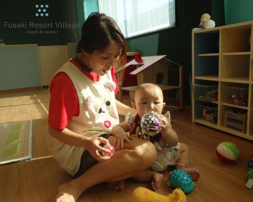 フサキの託児所で保育士とボールで遊ぶ女の子