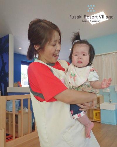 フサキの託児所で保育士に抱っこされる女の子