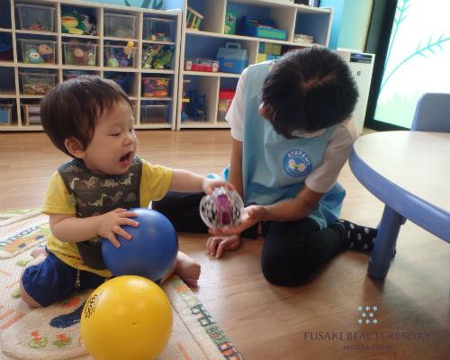 フサキの託児所でスタッフとボールで遊ぶ男の子