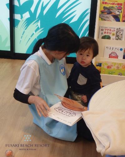 フサキの託児所で絵本を読む男の子
