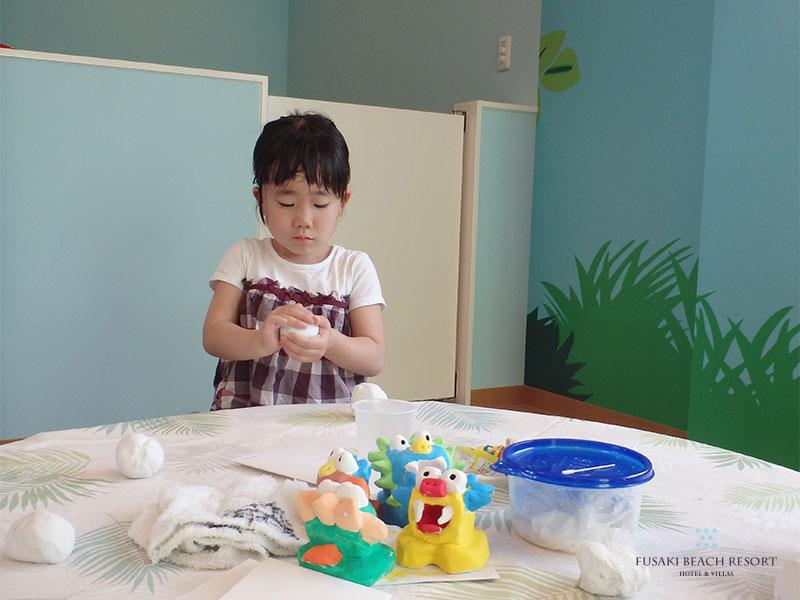シーサーづくり体験で紙粘土のシーサーを作る女の子