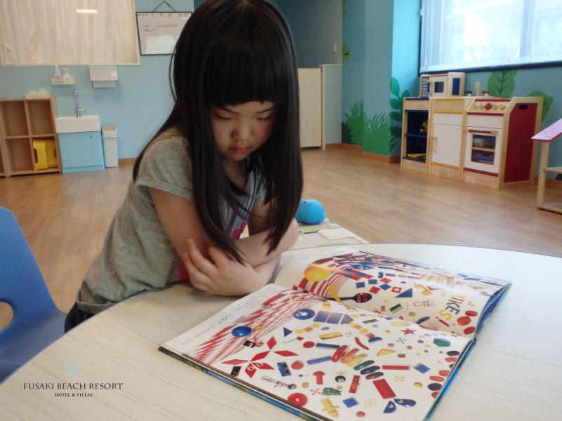 フサキの託児所で絵本を読む女の子