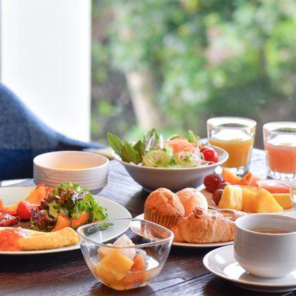 窓の外に緑が見える席でテーブルに並んだ朝食メニュー
